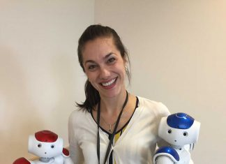 Jenay Beer, professor and researcher, holds robots used in IG pilot project