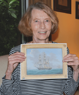 Pat McAlexander with picture of the ship that inspired her book.